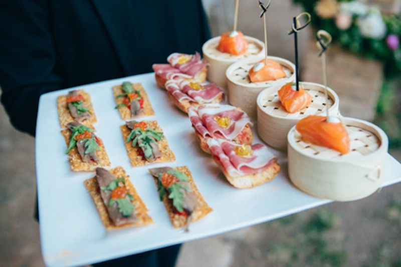 Tapas dishes in waiters hands including Iberico ham, salmon and coca bread with anchovy