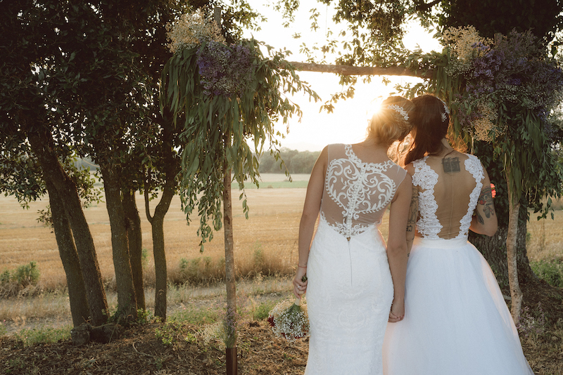 A lesbian couple in their wedding dresses holding hands looking at the sky