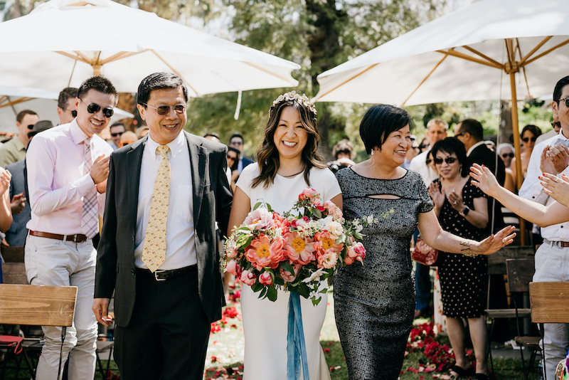 A bride walking down the aisle with both her mother and father