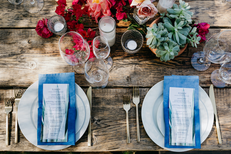 A wooden table set up for a wedding dinner with plates and glasses