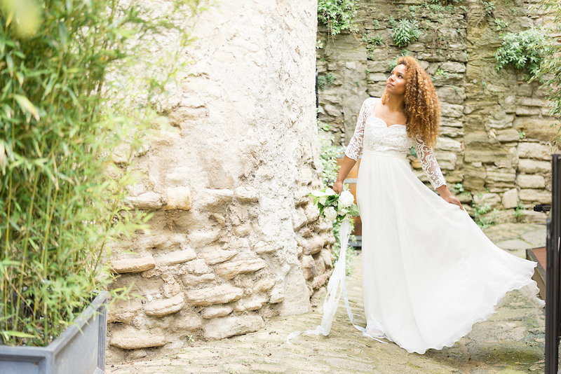 A bride wearing her wedding gown and posing outside a venue in Spain