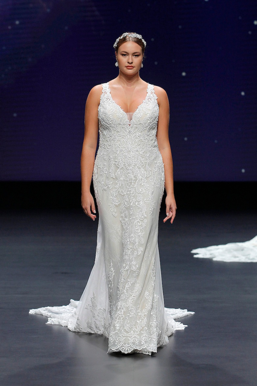 A Demetrios bridal model wearing a lace, tight dress