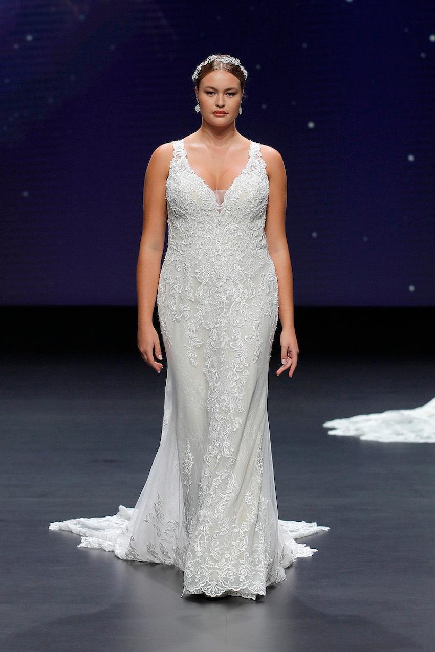 A Demetrios bridal model wearing a lace, tight dress