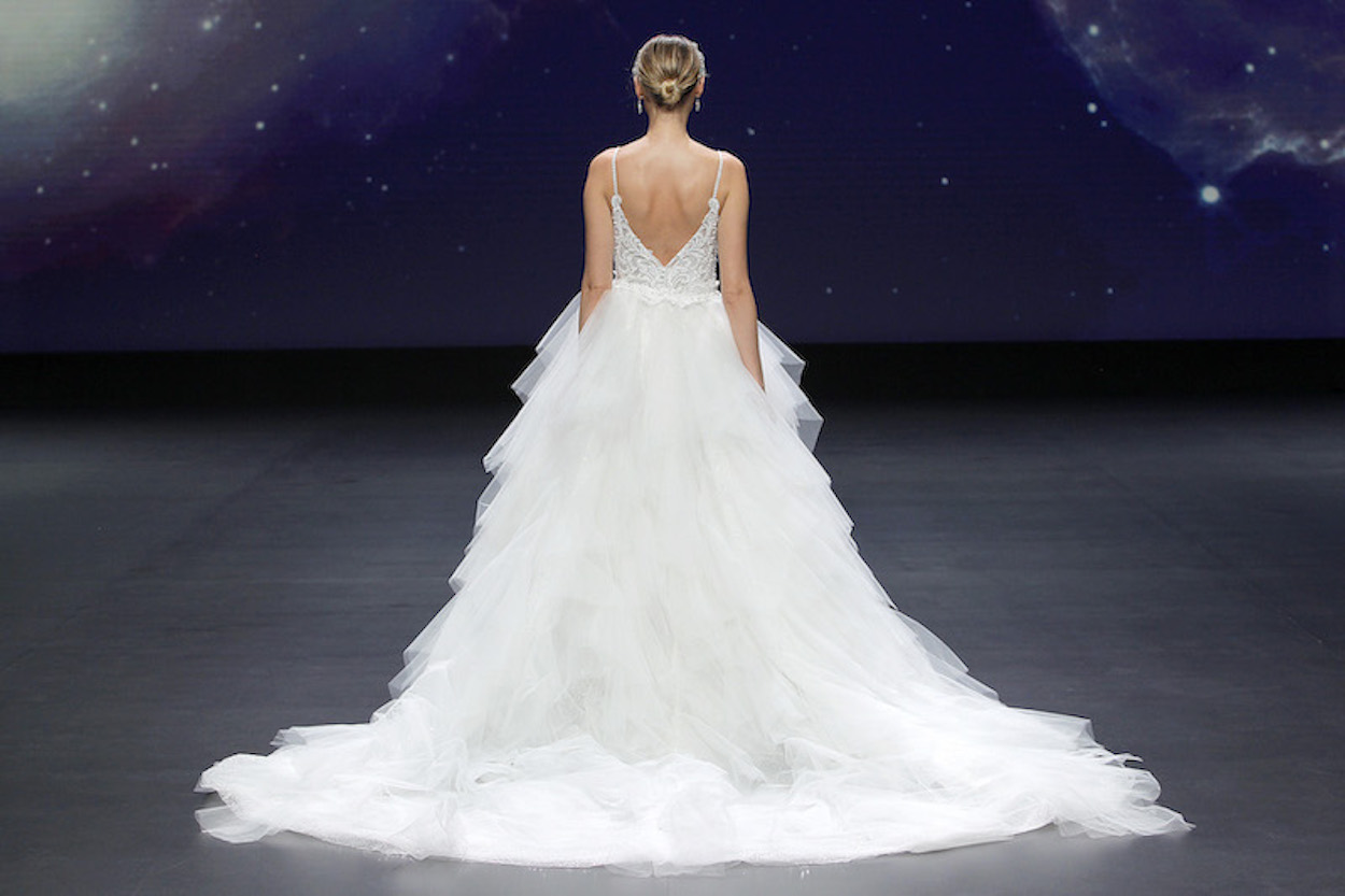 A Demetrios bridal model wearing a tiered skirt style of dress