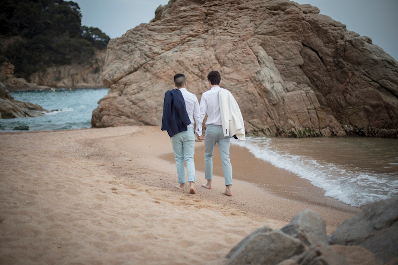 Two gay grooms holding hands and walking on the beach
