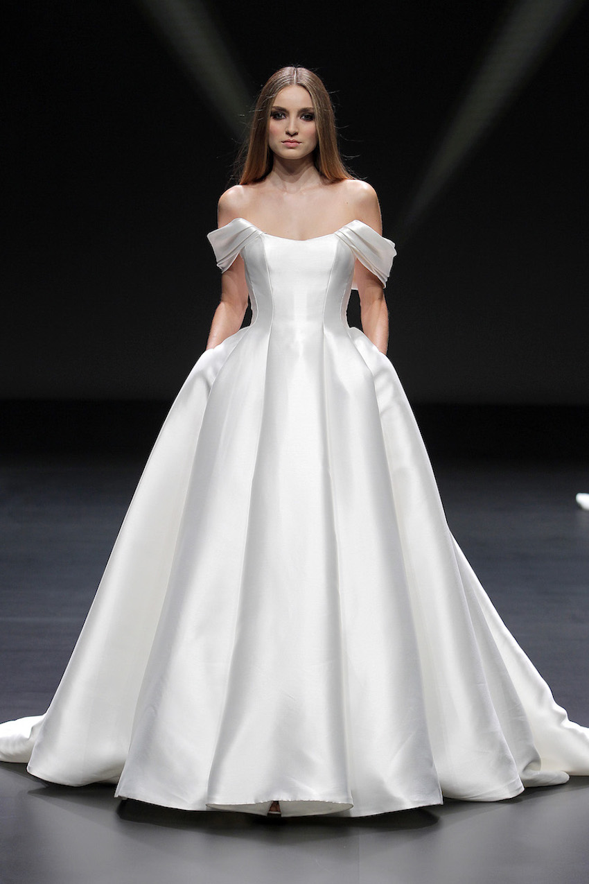 A Pronovias bridal model wearing a tight wasted and ballgown style dress