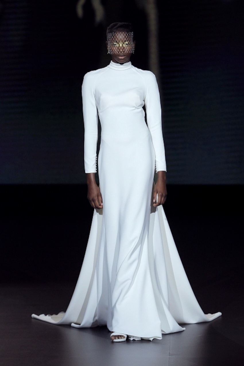 A Yolancris bridal model wearing a full length, long-sleeved minimalist dress