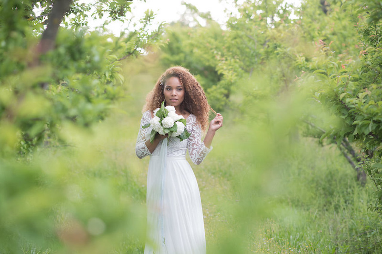 A bride outside in her bridal dress holding a wedding bouquet