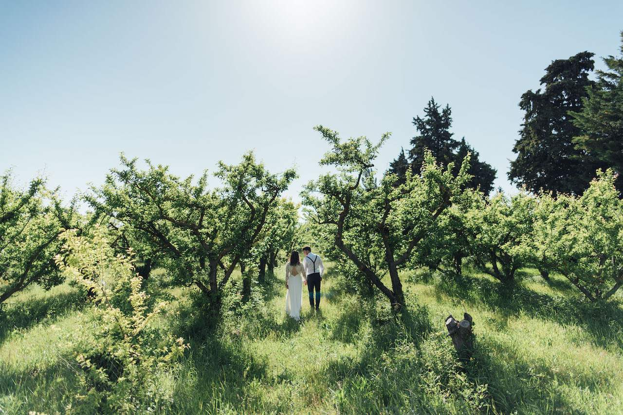 A bride and groom walking away in the countryside while holding hands