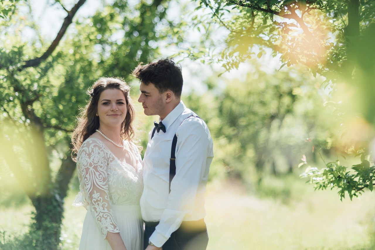 A bride and groom holding each other in a rural location