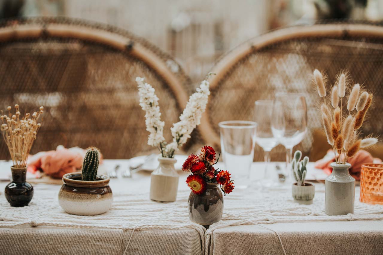 A table with potted plants and dried flowers